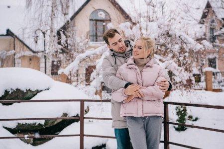 Photo pour Bel homme regardant joyeuse petite amie et des caresses en hiver - image libre de droit