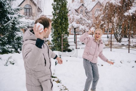 cheerful couple playing with snowballs in winter