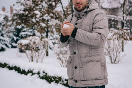 cropped view of man holding snowball in hands in winter