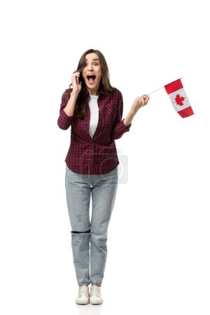 excited woman holding canadian flag and talking on smartphone isolated on white