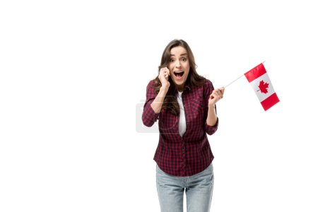 surprised woman holding canadian flag and talking on smartphone isolated on white