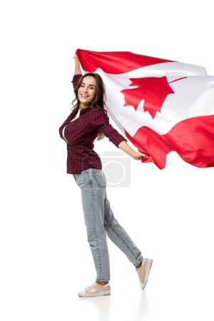 beautiful cheerful woman holding canadian flag and looking at camera isolated on white