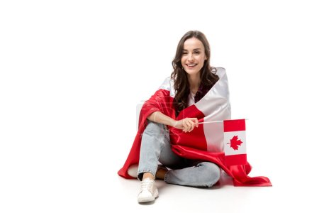 attractive woman covered in canadian flag holding maple leaf flag isolated on white
