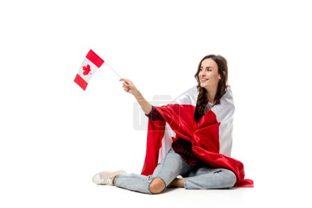 smiling woman covered in canadian flag holding maple leaf flag isolated on white