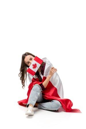 Photo pour Femme couverte du drapeau canadien tenant le drapeau de la feuille d'érable devant le visage isolé sur blanc - image libre de droit