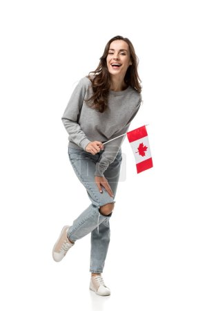 excited woman in grey casual clothes holding canadian flag and looking at camera isolated on white