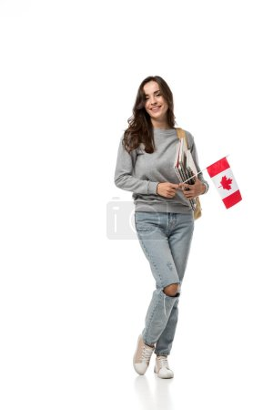 female student holding canadian flag and notebooks while looking at camera isolated on white