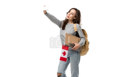 female student with notebooks holding canadian flag and taking selfie on smartphone isolated on white
