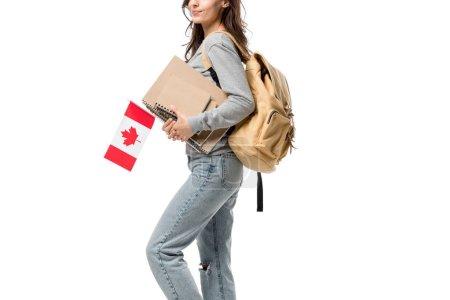 Photo pour Vue recadrée étudiante avec sac à dos et cahiers tenant le drapeau canadien isolé sur blanc - image libre de droit