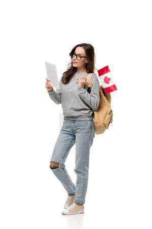 Photo pour Étudiante à lunettes tenant le drapeau canadien et à l'aide de tablette numérique isolé sur blanc - image libre de droit
