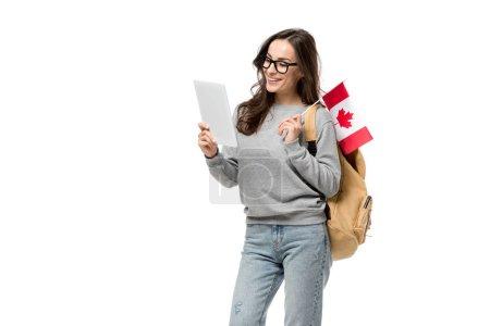 Photo pour Étudiante souriante dans les verres, tenant le drapeau canadien et à l'aide de tablette numérique isolé sur blanc - image libre de droit