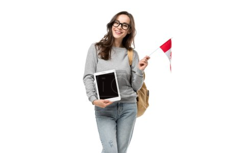 smiling female student holding canadian flag and presenting digital tablet with blank screen isolated on white