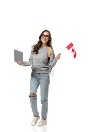 happy female student in glasses holding laptop and canadian flag isolated on white