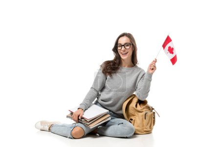 Foto de Estudiante feliz sentado con bandera canadiense y portátiles aislados en blanco - Imagen libre de derechos