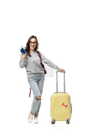 female student with suitcase holding passport and air tickets isolated on white, studying abroad concept