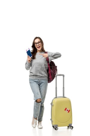 female student with suitcase pointing with finger at passport and air tickets isolated on white, studying abroad concept