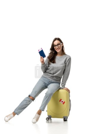 happy woman sitting on suitcase with passport and air tickets isolated on white, travel concept
