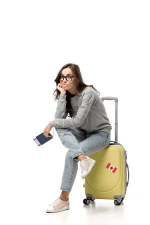 pensive woman sitting on suitcase with passport and air tickets isolated on white, travel concept