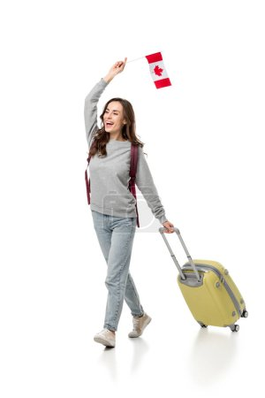 cheerful female student with suitcase and canadian flag isolated on white, studying abroad concept