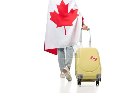 cropped view of woman covered in canadian flag with suitcase isolated on white, travel concept