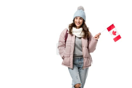 smiling female student in winter clothes holding canadian flag and looking at camera isolated on white
