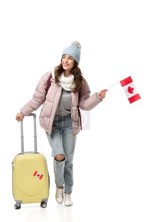female student in winter clothes with suitcase holding canadian flag isolated on white