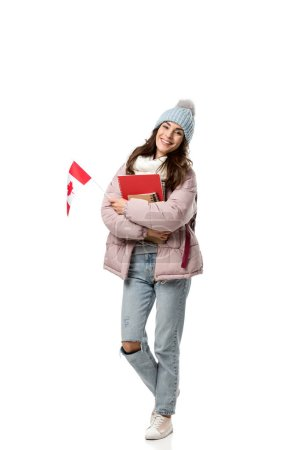 female student in winter clothes with canadian flag and notebooks isolated on white, studying abroad concept