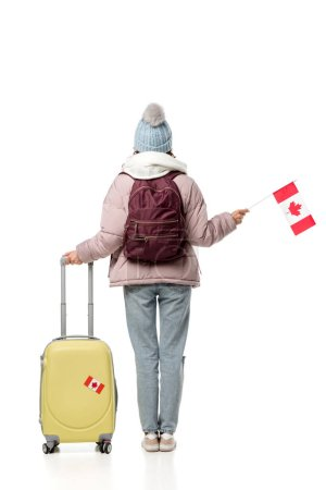 back view of female student in winter clothes with suitcase and canadian flag isolated on white, studying abroad concept