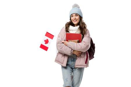 Foto de Feliz mujer estudiante de en ropa de invierno con la bandera canadiense y cuadernos aislados en blanco, concepto en el extranjero - Imagen libre de derechos