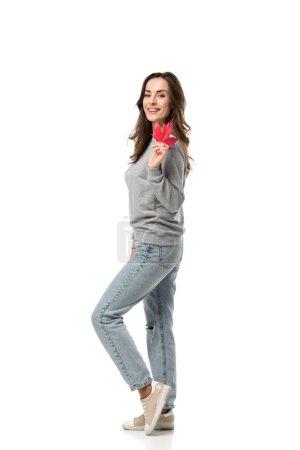 Photo pour Femme souriante en vêtements décontractés tenant feuille d'érable et regardant la caméra isolé sur blanc - image libre de droit