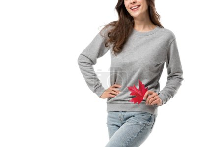 cropped view of woman in casual clothes holding maple leaf isolated on white