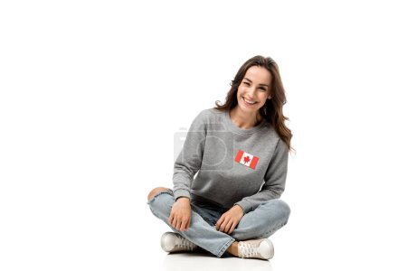 happy woman with canadian flag badge sitting and looking at camera isolated on white