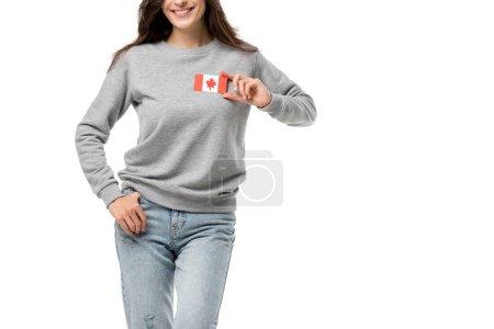 Photo pour Vue partielle de femme souriante avec insigne drapeau canadien isolé sur blanc - image libre de droit