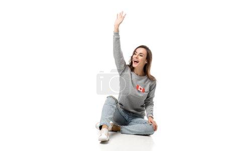 Photo pour Femme heureuse avec l'insigne du drapeau canadien assis et en agitant avec main isolé sur blanc - image libre de droit