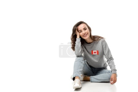 woman with canadian flag badge sitting and looking at camera isolated on white
