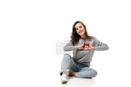 woman sitting and showing heart symbol with hands over canadian flag badge isolated on white