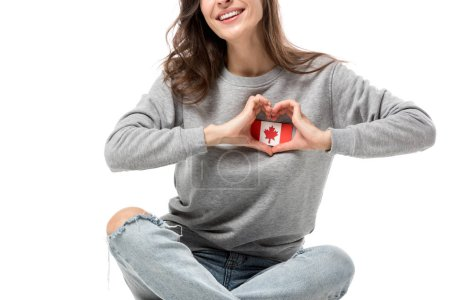 cropped view of woman showing heart symbol with hands over canadian flag badge isolated on white