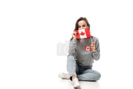 Photo pour Femme avec maple leaf insigne, le tout assis tenant le drapeau canadien isolé sur blanc - image libre de droit