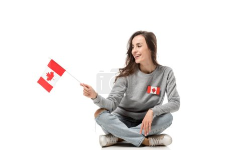 smiling woman with maple leaf badge sitting and holding canadian flag isolated on white
