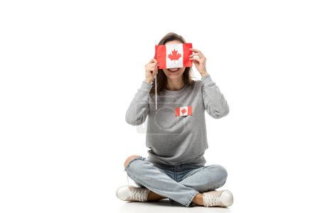 woman with maple leaf badge sitting and holding canadian flag in front of face isolated on white