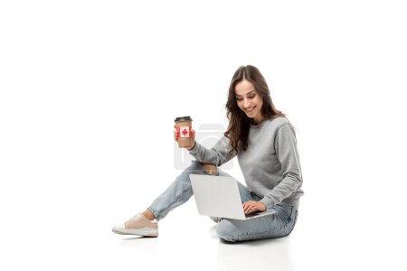 smiling woman using laptop and holding coffee cup with canadian flag sticker isolated on white