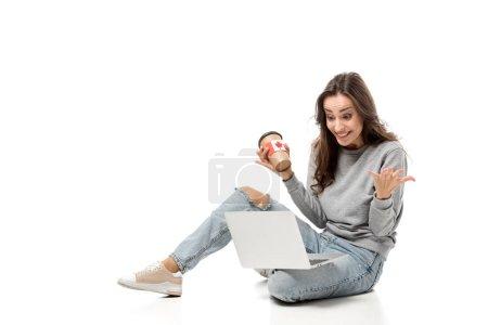 Photo pour Femme surprise utilisant un ordinateur portable et tenant une tasse de café avec autocollant drapeau canadien isolé sur blanc - image libre de droit