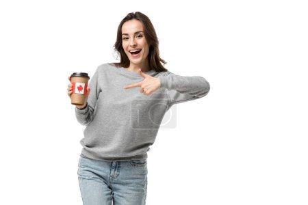 Photo pour Femme souriante, pointant avec le doigt à la tasse de café avec autocollant drapeau canadien isolé sur blanc - image libre de droit