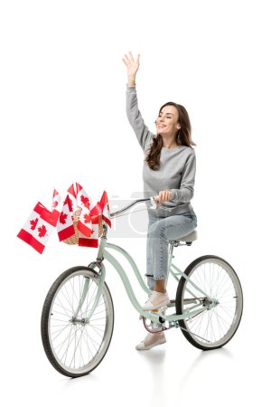 Photo for Woman waving and riding vintage bicycle with canadian flags isolated on white - Royalty Free Image