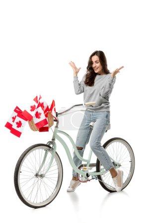 Photo for Woman gesturing with hands and riding vintage bicycle with canadian flags isolated on white - Royalty Free Image