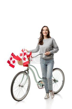 Foto de Bella mujer sonriente con bicicleta vintage y banderas canadienses aislados en blanco - Imagen libre de derechos