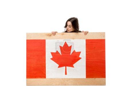 Photo pour Femme assise derrière la planche de bois avec le drapeau canadien et à la recherche de suite isolé sur blanc - image libre de droit