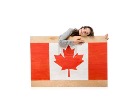 woman with eyes closed holding wooden board with canadian flag isolated on white