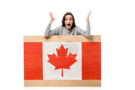 surprised woman gesturing with hands behind wooden board with canadian flag isolated on white
