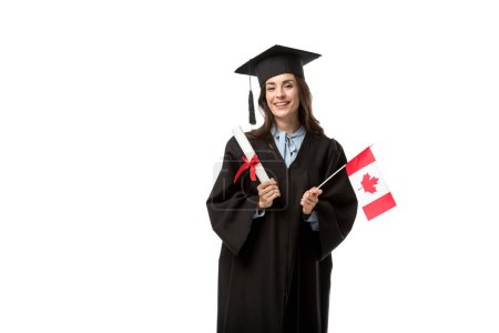 female student in academic gown looking at camera and holding canadian flag with diploma isolated on white